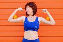 Female power, freshness and wellness: fit woman in blue sports bra standing and checking muscles with two oranges on her biceps royalty free stock photography