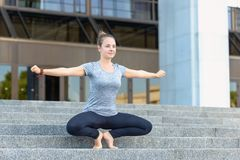 Female practice baddha konasana, butterfly pose on toes with han. Young woman practicing vajra yoga in city. Female practice baddha konasana, butterfly pose on Royalty Free Stock Images