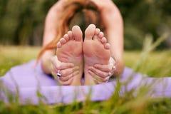 Female practicing paschimottanasana yoga on grass Royalty Free Stock Photos