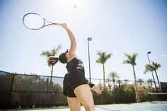 Female practicing tennis on a summer day. Young female tennis player hitting ball whilst practising on tennis court on a summer day Royalty Free Stock Photo