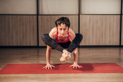 Female practicing yoga in a studio setting. Beautiful young woman doing yoga exercise on mat stock photography
