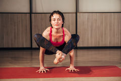 Female practicing yoga in a studio setting. Beautiful young woman doing yoga exercise on mat royalty free stock images