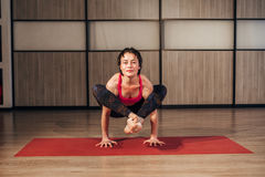 Female practicing yoga in a studio setting. Beautiful young woman doing yoga exercise on mat stock photo