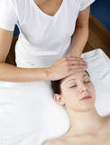 Female practitioner at a beauty spa. Facial massage for stress relief Royalty Free Stock Images