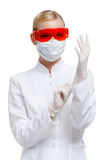 Female practitioner puts on medical gloves Royalty Free Stock Photos
