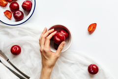 Female preparing red plums for afternoon snack. Horizontal, still life food scene featuring shiny red plums in white dishes on white table Royalty Free Stock Image