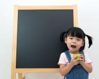 Female preschooler with apple in hand Stock Photo