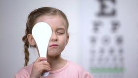 Female preschooler closing eye for complete vision exam, diagnostics of sight