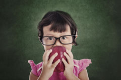 Female preschooler eats red apple Royalty Free Stock Photo