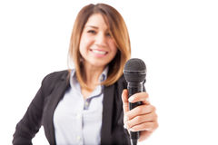 Female presenter handing over the microphone. Happy female presenter in a suit handing over the microphone. Focus on microphone stock photography