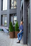 Female pretty model wearing blue shirt and jeans, standing near building and green plant. royalty free stock photography