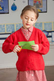 Female Primary School Pupil Cutting Shapes royalty free stock photography
