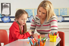 Female Primary School Pupil And Teacher Working. At Desk In Classroom royalty free stock images