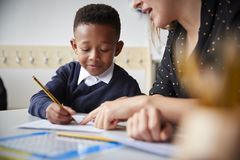 Female primary school teacher helping a young school boy sitting at table in a classroom, close up, selective focus royalty free stock photography