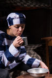 Female prisoner blowing on hot tea in an aluminum cup in a small Royalty Free Stock Images