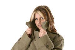 Female Private Eyes. Female private detective peering over her trench coat royalty free stock photo