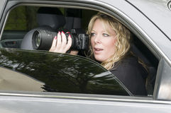 Female private investigator with camera. Female private investigator or spy or secret agent taking photographs from car stock images