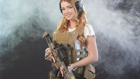 Female private military contractor dressed in tactical uniform armed with riffle, slow motion. Beautiful caucasian female private military contractor with long stock video