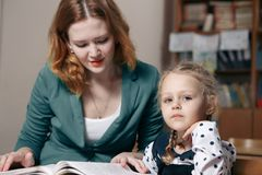 Female private tutor helping young student with homework at desk in bright child`s room. Female private tutor helping young student with homework at desk in Royalty Free Stock Photos