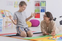 Private tutor working with child. Female private tutor working with little boy teaching child to read using colorful letters Stock Photo