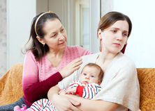Female problems. Mature mother asks for forgiveness from daught. Female problems. Mature mother asks for forgiveness from adult daughter with baby after quarrel Royalty Free Stock Photography