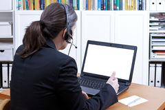 Female professional headset copy space. Female professional with headset in front of a laptop talking to someone during an online video call, empty screen Royalty Free Stock Photography