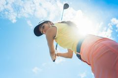 Female professional player holding up the iron club while playing golf. Low-angle view of a female professional player holding up the iron club with Royalty Free Stock Image