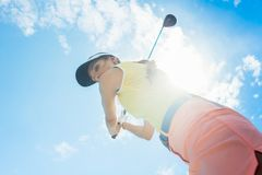 Female professional player holding up the iron club while playing golf. Low-angle view of a female professional player holding up the iron club with Stock Photos