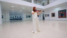 Female professional is playing the violin in the gallery. 4K stock footage