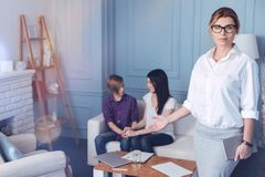 Female professional psychologist posing with loving family in background. There is now trouble that cannot be solved. Selective focus on serious psychotherapist Stock Photography