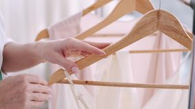 A female professional tailor is appreciating a dress on a hanger