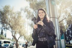 Female professional videographer travel photographer making video in 4K resolution trough of the streets. Holding 3 axis gimbal stabilizer.Filming with royalty free stock photos