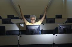 Female Professor Celebrating Victory In Computer Classroom Royalty Free Stock Image