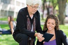 Female Professor Helping Grad Student. University professor helping grad student using digital tablet Royalty Free Stock Photography