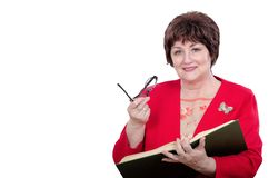 Female professor in red jacket. Portrait of cheerful female professor holding big book with left hand and glasses by right. Adult mature woman wears red jacket stock image