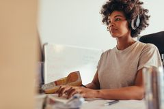 Female programmer typing data codes. Working on project in software development company. African woman wearing headphones concentrating while working on stock images