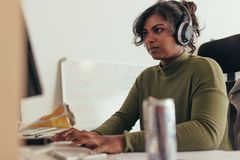 Programmer developing new program coding. Female programmer working in a software developing company office. Woman wearing headphones coding on desktop computer royalty free stock images