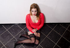 Female prostitute sitting on the floor Stock Images