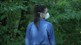Female in protective mask looking camera standing forest, harmful chemicals