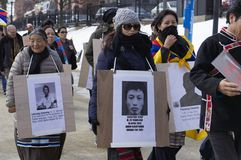 Female protestors marching. Boston, Massachusetts USA - March 2013 - Group of protesters wearing pictures of political casualties during the Boston Free Tibet Stock Images