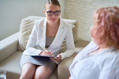 Female Psychiatrist Listening to Obese Patient. Portrait of beautiful young women writing on clipboard while listening to  obese women during therapy session on Royalty Free Stock Photography