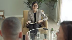 Female psychoanalyst talking with married couple trying to solve their relationship difficulties. Marriage counseling. stock footage