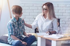 Female psychologist allaying unrest of a youngster. You can trust me. Careful psychology professional putting her hand on a shoulder of a young patient while Royalty Free Stock Photos