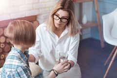 Female psychologist giving glass of water to child patient. Take some water. Worried female professional trying to calm a teenage patient down while talking Stock Photography