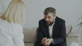 Female psychologist giving paper napkin to crying businessman patient and calm him down in her office. Indoors stock footage