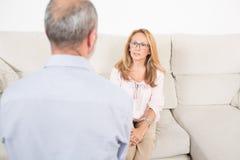 Female psychologist listening to elderly man Stock Photos