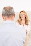 Female psychologist listening to elderly man Royalty Free Stock Image