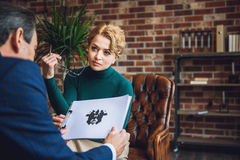 Female psychologist looking at patient with expectation. Attentive women is sitting on chair. She holding glasses. Mature men keeping rorschach test Stock Image