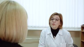 Female psychologist making notes during psychological therapy session. Female psychologist communicates with a woman of 45 years. Session of psychotherapy stock video