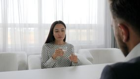 Female at psychologist talk about problems, conversation of Men and women in Office space,. Portrait of miserable woman Seated on table at psychotherapist stock video footage
